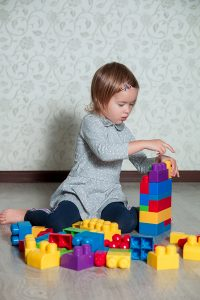Child girl having fun and build of bright plastic construction blocks. Toddler playing on the floor. Developing toys. Early learning.