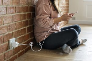 Young woman using a smartphone as it is being charged