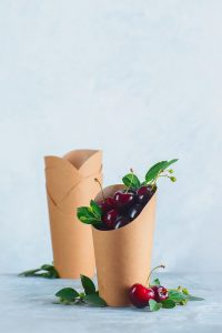 Craft paper eco-friendly food packaging with cherries. Disposable cups on a neutral gray background with copy space. Preserving nature and recycling concept.